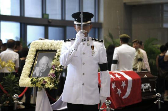 A vigil guard takes his position as members of the public pay their respects to the late Lee Kuan Yew at the Parliament House where he will lie in state for four days, Thursday, March 26, 2015, in Singapore. Lee, 91, died Monday at Singapore General Hospital after more than a month of battling severe pneumonia. The government declared a week of mourning for the leader who is credited with transforming the resource-poor island into a wealthy finance and trade hub with low crime and corruption in a region saddled with graft, instability and poverty. (AP Photo/Wong Maye-E)