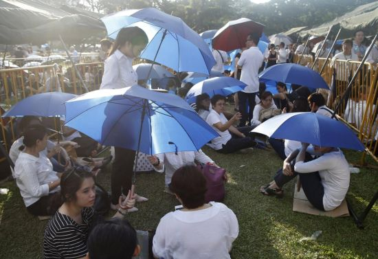 People sit under umbrellas, as they queue up to pay their respects to the late first prime minister Lee Kuan Yew, at the Parliament House in Singapore, March 27, 2015. Thousands of Singaporeans queued to pay their last respects to former prime minister Lee Kuan Yew, who lay in state at Parliament House, waiting for up to ten hours in stifling tropical heat to view his body. REUTERS/Edgar Su