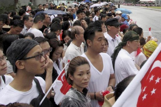 Singaporeans wait for the coffin of Lee Kuan Yew to pass during the funeral procession, Sunday, March 29, 2015, at the Padang parade grounds and City Hall in Singapore. Tens of thousands of Singaporeans undeterred by heavy rains lined a 15 kilometer (9 mile) route through the Southeast Asian city-state to witness an elaborate funeral procession Sunday for longtime leader Lee Kuan Yew, who died Monday at 91. (AP Photo/Jeanette Tan)