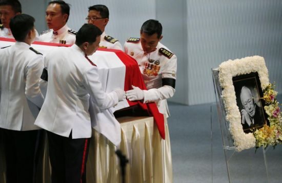Pallbearers adjust the national flag of Singapore covering the coffin of the late Lee Kuan Yew during a state funeral held at the University Cultural Center, Sunday, March 29, 2015, in Singapore. During a week of national mourning that began Monday after Lee's death at age 91, some 450,000 people queued for hours for a glimpse of Lee's coffin at Parliament House. A million people visited tribute sites at community centers across the island and leaders and dignitaries from more than two dozen countries attended the state funeral. (AP Photo/Wong Maye-E)