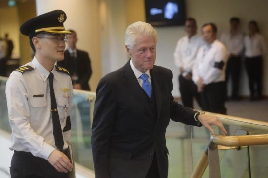 Former U.S. president Bill Clinton, right, arrives at the state funeral for the late Lee Kuan Yew, at the University Cultural Center, Sunday, March 29, 2015 in Singapore. During a week of national mourning that began Monday after Lee's death at age 91, some 450,000 people queued for hours for a glimpse of Lee's coffin at Parliament House. A million people visited tribute sites at community centers across the island and leaders and dignitaries from more than two dozen countries attended the state funeral. (AP Photo/Joseph Nair)