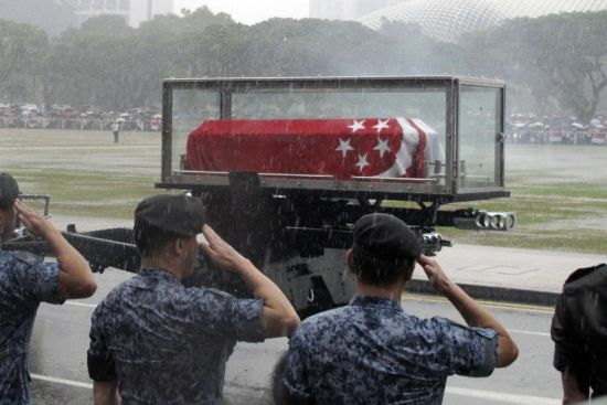 Standing in a downpour, Singaporean soldiers salute as the coffin of Lee Kuan Yew passes during the funeral procession, Sunday, March 29, 2015, at the Padang parade grounds and City Hall in Singapore. Tens of thousands of Singaporeans undeterred by heavy rains lined a 15 kilometer (9 mile) route through the Southeast Asian city-state to witness an elaborate funeral procession Sunday for longtime leader Lee Kuan Yew, who died Monday at 91. (AP Photo/Jeanette Tan)