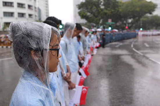 Singaporeans wait for the coffin of Lee Kuan Yew to pass during the funeral procession, Sunday, March 29, 2015, at the Padang parade grounds and City Hall in Singapore. Tens of thousands of Singaporeans undeterred by heavy rains lined a 15 kilometer (9 mile) route through the Southeast Asian city-state to witness an elaborate funeral procession Sunday for longtime leader Lee Kuan Yew, who died Monday at 91.