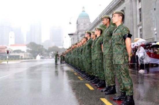 Standing in a downpour, Singaporean soldiers stand at attention during a 21-gun salute as the coffin of Lee Kuan Yew passes during the funeral procession, Sunday, March 29, 2015, at the Padang parade grounds and City Hall in Singapore.