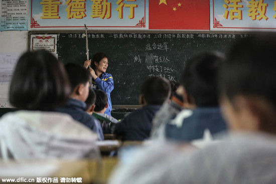 Zhu Youfang, who suffers from an illness hampering her motor functions, hangs on to a rope in order to stand while she teaches her class at Shangluo school in Chengui town of Daye, Central China's Hunan province on March 30, 2015. Zhu, who has 31 years of teaching experience, has persisted teaching despite her poor health conditions over the last three years. [Photo/IC]