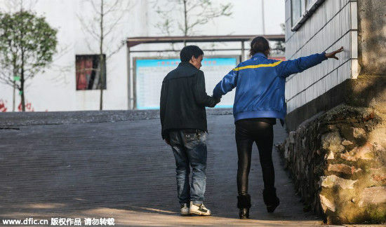 Zhu walks with the help of her husband, who works in the same school as Zhu. Zhu has difficulties standing, raising her hands, turning her head and doing other movements, and has to support herself with a wall or handrail when she walks. [Photo/IC]