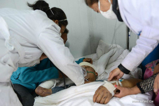 Medical staff members treat an injured Nepalese at Zham Town in Nyalam County, southwest China's Tibet Autonomous Region, April 28, 2015. Rescuers have cleared a highway leading into the Tibetan town where thousands of people were trapped following the 7.9-magnitude earthquake in Nepal Saturday. (Xinhua/Chogo)