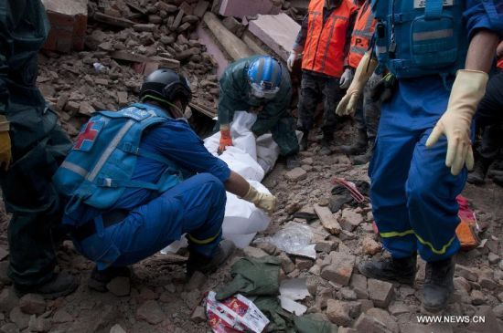 Chinese rescuers find the body of a victim from debris in Sankhu on the outskirts of Kathmandu, Nepal, April 30, 2015. As a responsible global power and Nepal's neighbor, China responded immediately to Nepal's call after the magnitude-7.9 quake hit Nepal, leaving more than 5,000 people dead and many more still missing. [Photo/Xinhua]