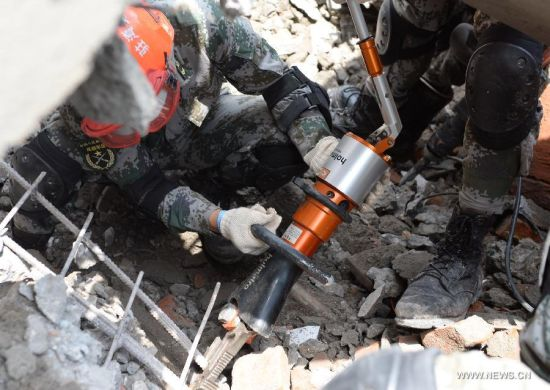 Chinese rescuers work at a building collapse site on the outskirts of Kathmandu, Nepal, April 30, 2015. As a responsible global power and Nepal's neighbor, China responded immediately to Nepal's call after the magnitude-7.9 quake hit Nepal, leaving more than 5,000 people dead and many more still missing. [Photo/Xinhua]