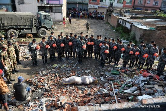Chinese rescuers mourn after finding the body of a victim at a building collapse site on the outskirts of Kathmandu, Nepal, April 30, 2015. As a responsible global power and Nepal's neighbor, China responded immediately to Nepal's call after the magnitude-7.9 quake hit Nepal, leaving more than 5,000 people dead and many more still missing.[Photo/Xinhua]