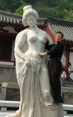 A tourist takes a photo with the statue of Concubine Yang touching her breast.