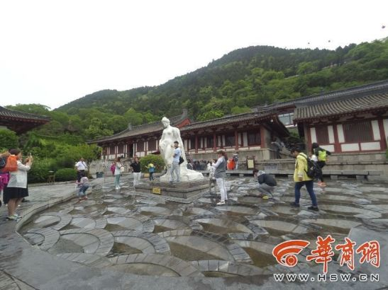 Tourists take off their shoes and wash their feet in the pool below the statue.