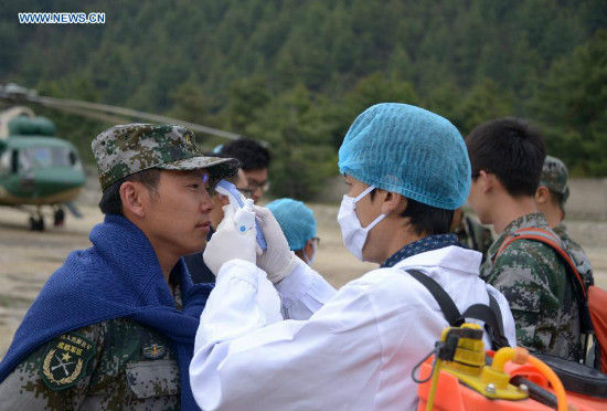 An inspection and quarantine worker measures body temperature for a helicopter crew member in Gyirong County, southwest China's Tibet Autonomous Region, May 6, 2015. Three helicopters from China's air force flew to Nepal on Wednesday morning to help with transportation and rescue. (Xinhua/Wang Shoubao)