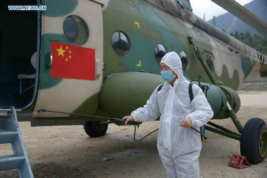 An inspection and quarantine worker sanitizes a helicopter in Gyirong County, southwest China's Tibet Autonomous Region, May 6, 2015. Three helicopters from China's air force flew to Nepal on Wednesday morning to help with transportation and rescue. (Xinhua/Wang Shoubao)
