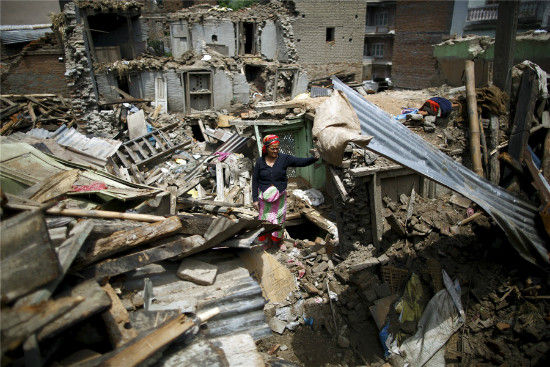 A woman stands on the debris of collapsed houses after a fresh 7.3-magnitude earthquake struck Nepal, in Sankhu May 12, 2015. The earthquake killed at least 47 people and spread panic in Nepal on Tuesday, bringing down buildings already weakened by a devastating tremor less than three weeks ago and unleashing landslides in Himalayan valleys near Mount Qomolangma. [Photo/Agencies]