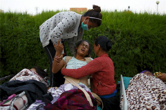 An earthquake victim reacts in pain after being moved out from the hospital to the open ground for treatment, in Kathmandu, May 12, 2015. [Photo/Agencies]