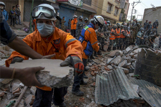 Nepalese military personnel remove debris in search of survivors after a fresh 7.3 earthquake struck, in Kathmandu, Nepal, May 12, 2015. [Photo/Agencies]