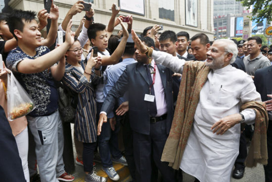 India's Prime Minister Narendra Modi waves to local residents in Xi'an, Shaanxi province. [Photo by Feng Yongbin/China Daily]