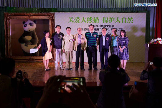 Guests pose for a photo at an activity celebrating the 35th birthday for giant panda Basi at a giant panda research center in Fuzhou, capital of southeast China's Fujian Province, May 21, 2015. Basi, the equivalent of over 100 years in human age, is the oldest living giant panda in Chinese mainland. (Xinhua/Jiang Kehong)