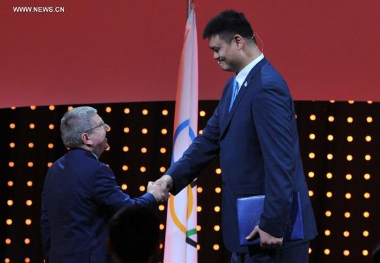 International Olympic Committee (IOC) President Thomas Bach (L) shakes hands with Yao Ming, three-time Olympian, seven-time NBA ALL star, and Beijing 2022 ambassador and member of the Beijing 2022 Olympic Winter Games presentation delegation, at the 128th IOC session in Kuala Lumpur, Malaysia, on July 31, 2015. The session will decide the host cities of the 2022 Olympic Winter Games and the 2020 Youth Olympic Winter Games. (Xinhua/Gong Lei)