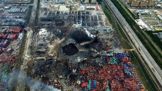 An aerial photo taken on Aug. 14, 2015 shows a huge hole at the core area of explosion site in Tianjin, north China. The death toll from explosions occurred on Wednesday night rises to 85 as of Saturday morning. (Xinhua)