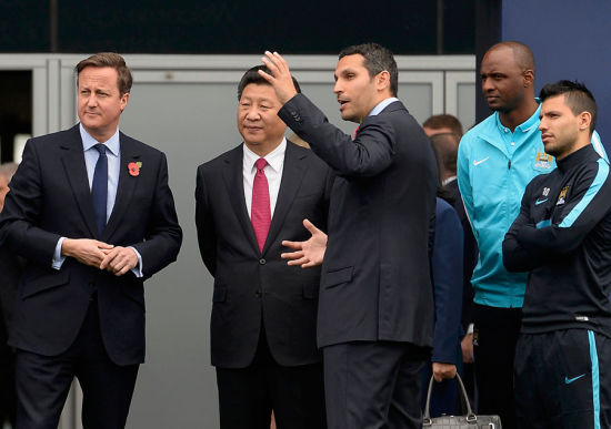 Britain's Prime Minister David Cameron (L) stands with President Xi Jinping (C) and Manchester City Chairman Khaldoon Al Mubarak (3rd R) during a visit to the City Football Academy in Manchester, Britain October 23, 2015. [Photo/Agencies]