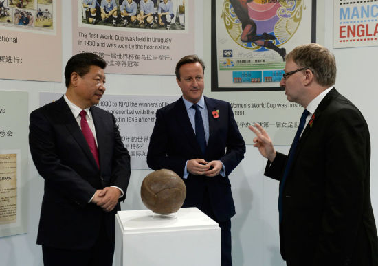 Britain's Prime Minister David Cameron and President Xi Jinping view the football used in the first World Cup final during a visit to the City Football Academy in Manchester, Britain Oct 23, 2015. [Photo/Agencies]