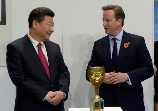 Britain's Prime Minister David Cameron and China's President Xi Jinping view the Jules Rimet trophy during a visit to the City Football Academy in Manchester, Britain Oct 23, 2015. [Photo/Agencies]