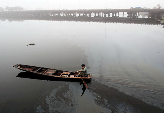 A man rows a boat through an oil slick on a lake in Shaoxing, Zhejiang province, on March 16. Fuel leaking from ships severely contaminates the quality of the water in the lake. [Photo by Li Ruichang/China Daily]