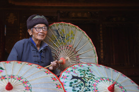 Zheng Yinghai, who is 90 years old, poses for a photo with umbrellas he made by hand. [Photo by Xu Jing/chinadaily.com.cn]