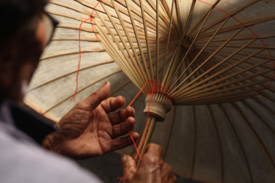 Zheng makes oiled paper umbrella totally by hand. [Photo by Xu Jing /chinadaily.com.cn]