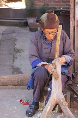 The elder Zheng uses traditional tools to cut bamboo chips in his courtyard. [Photo by Xu Jing/chinadaily.com.cn]
