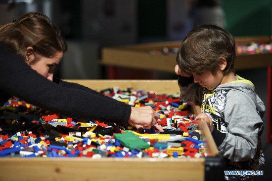 A mother and her son play Lego at the experience area at the exhibition