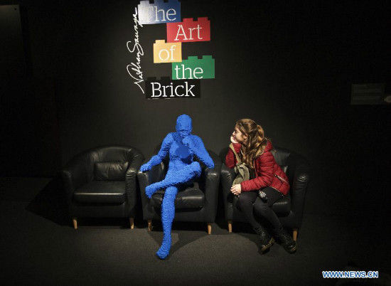 A visitor takes a photo with Blue Guy Sitting, an artwork by American artist Nathan Sawaya, at the exhibition