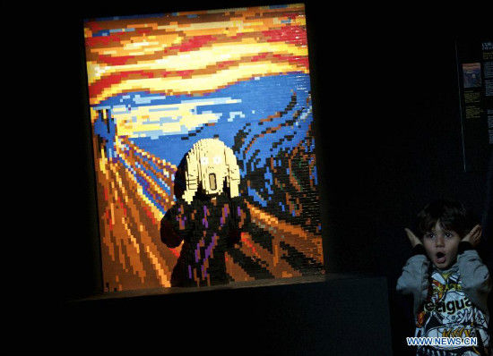 A visitor imitates the figure in Scream, an artwork by American artist Nathan Sawaya, at the exhibition