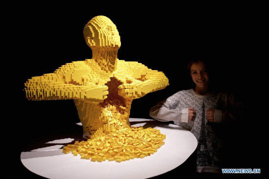 A visitor takes a photo with Yellow, an artwork by American artist Nathan Sawaya, at the exhibition