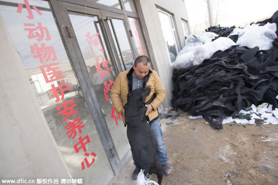 Wang Yan and a dog at the door of the rescue base.