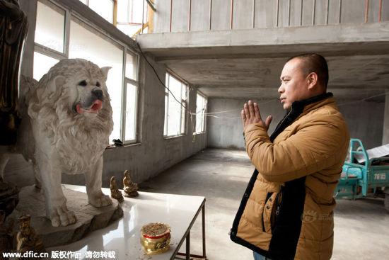 Wang Yan worships a dog statue at the rescue base.
