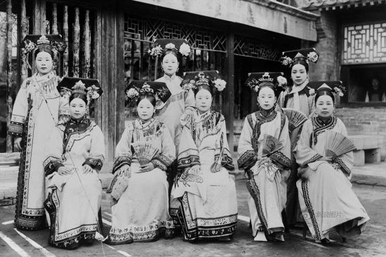 """Women of Manchu ethnicity has their own tradition of dressing, their iconic Qizhuang, hairstyle and """"high heel"""" shoes are standard clothing in the palace in Qing Dynasty (1644-1912).This photo shows Manchu women in the palace near the end of the Qing Dynasty."""