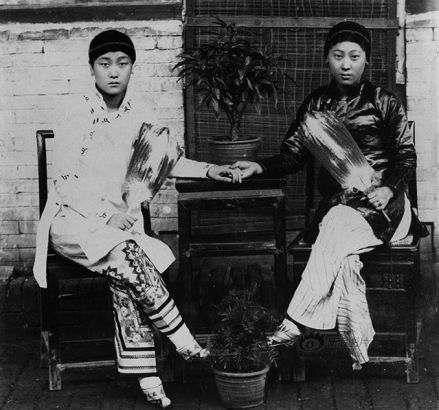 As western culture spread to China in the early 20th century, women's fashion was also influenced by the trend. Low collars grew taller, baggy gowns became tighter jackets, the beauty of women's figure was more and more stressed. Prostitutes were among those who stuck tightly with the fashion trends. This photo shows two women with bound feet in a brothel in the early Republic of China period (around 1911).