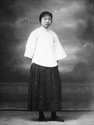 """This young woman was dressed in a typical student uniform in the period of the May 4th Movement (1915 - 1921). It even had a name called """"New Clothes of Civilization"""". The uniform first appeared in 1913, composed mainly of a short coat and a long skirt. In 1919, during the May 4th Movement, it was slightly changed to a short bluish coat and a black skirt, usually dressed with white cotton socks and black cloth shoes. In 1920, it was already the fashion icon of the epoch."""