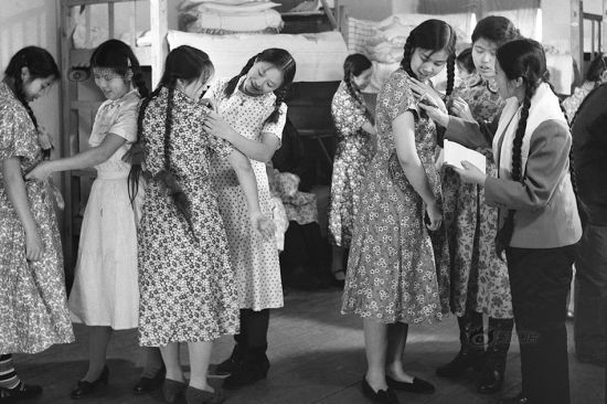"""""""Blazy"""" (платье), a dress with a shirt-like top, also came from the Soviet Union. It was so popular that some women workers would even save money for months to make one at the tailor's. Small girls in the kindergarten were also dressed in this way sometimes. The photo shows female wokers in the Harbin Linen Textile Mill trying on their """"Blazy""""s. Photo/Xinhua News Agency"""