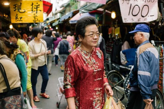 A formally-dressed lady walks in the Zhufuli market in Taipei. The market was originally a militant dependents' village. It was conversed into a residential building, and then turned into a market.