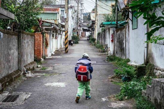 """A child comes back to the Beitou village after school. He is among the fifth generation villagers here. The """"bamboo fences"""" have long disappeared in the militant dependents' villages. Mainland snacks such as Shandong Steamed Bun and Beef Noodles are no longer specialties of the villages."""