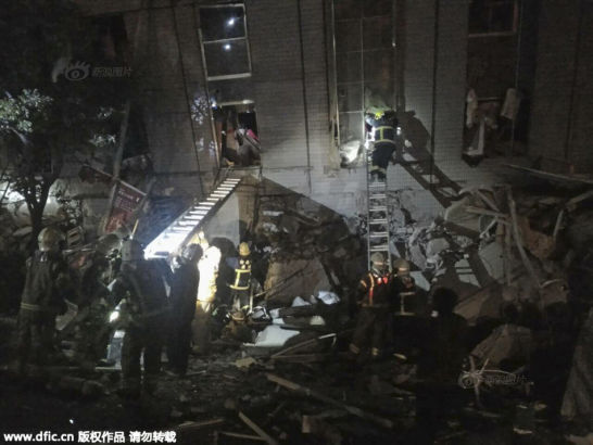 Rescuers are seen entering an office building that collapsed on its side from an early morning earthquake in Tainan, southern Taiwan, Saturday, Feb. 6, 2016. A 6.4-magnitude earthquake has struck southern Taiwan, according to the U.S. Geological Survey.