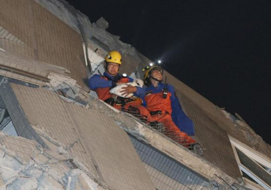 Rescue workers carry a baby swaddled in a cloth from the rubble of a toppled building after an earthquake in Tainan, Taiwan, Saturday, Feb. 6, 2016. The 6.4-magnitude earthquake struck southern Taiwan early Saturday, toppling at least one high-rise residential building and trapping people inside. Firefighters rushed to pull out survivors. (AP Photo) TAIWAN OUT