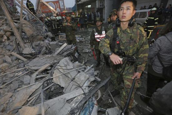 Army soldiers search a toppled building an earthquake in Tainan, Taiwan, Saturday, Feb. 6, 2016. The 6.4-magnitude earthquake struck southern Taiwan early Saturday, toppling at least one high-rise residential building and trapping people inside. (AP Photo) TAIWAN OUT