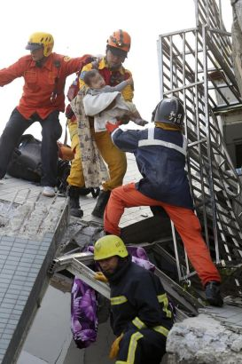 A child is rescued from a toppled building after a 6.4-magnitude earthquake in Tainan, Taiwan, Saturday, Feb. 6, 2016. The earthquake struck southern Taiwan early Saturday, toppling at least one high-rise residential building and trapping people inside. (AP Photo) TAIWAN OUT