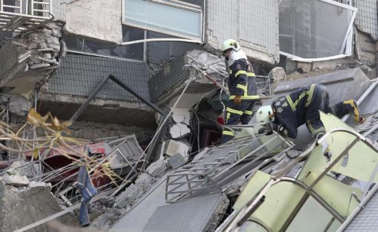 Emergency rescue teams search for victims in a collapsed building after a 6.4-magnitude earthquake in Tainan, Taiwan, Saturday, Feb. 6, 2016. The earthquake struck southern Taiwan early Saturday, toppling at least one high-rise residential building and trapping people inside. (AP Photo) TAIWAN OUT