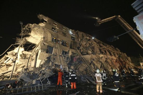 Rescue workers search a toppled building after an earthquake in Tainan, Taiwan, Saturday, Feb. 6, 2016. The 6.4-magnitude earthquake struck southern Taiwan early Saturday, toppling at least one high-rise residential building and trapping people inside. Firefighters rushed to pull out survivors. (AP Photo) TAIWAN OUT